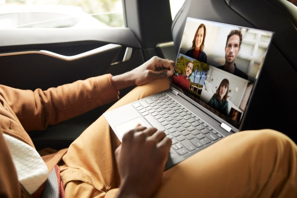 Someone sitting in the backseat of car using the Lenovo Yoga 5G laptop. Screen shows a live video conference.