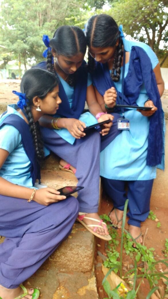 Students viewing Meghshala lessons on a Lenovo tablet.
