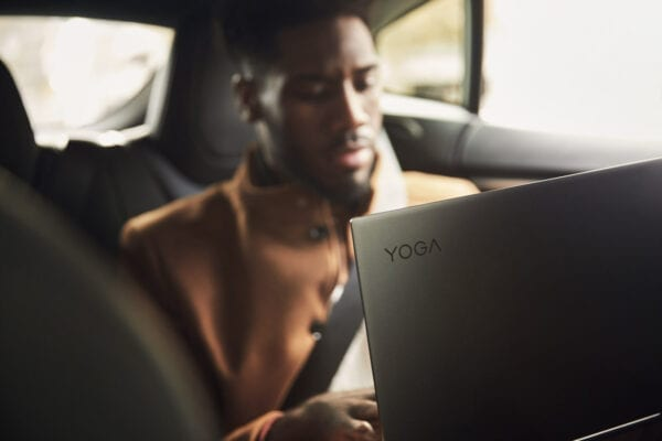 Man sitting in the backseat of a car using a Lenovo Yoga 5G laptop.
