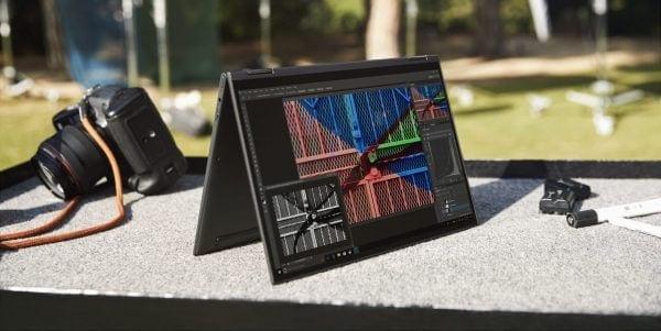 Lenovo Yoga 5G in tent mode beside a DSLR camera