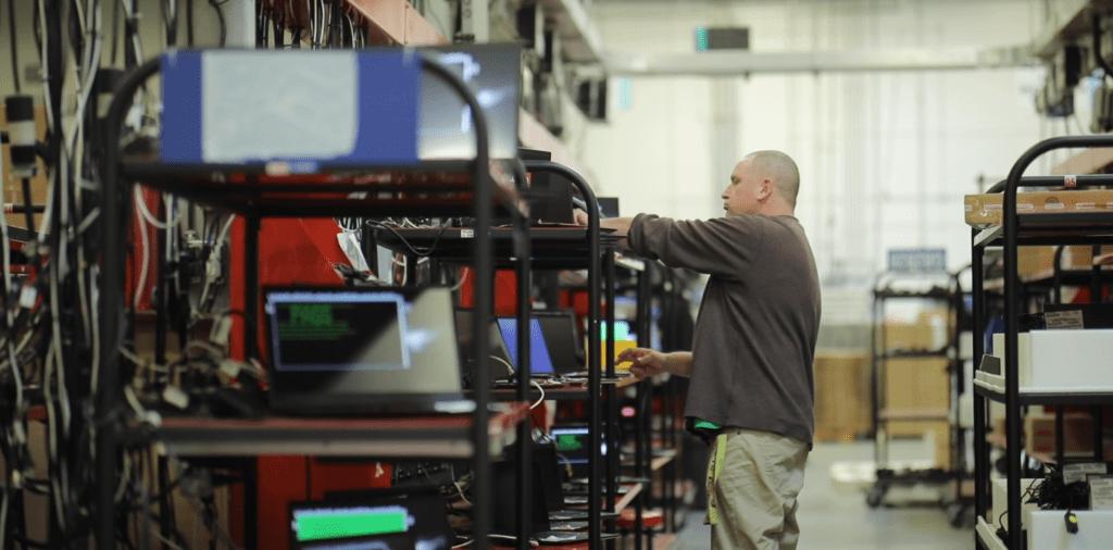 Lenovo employee checking racks of PCs in the Whitsett warehouse