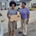 USCRI student receiving donated Lenovo PC for distance learning