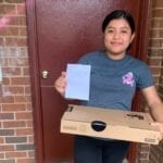 USCRI student and rising 9th grader Julissa receiving her Lenovo PC
