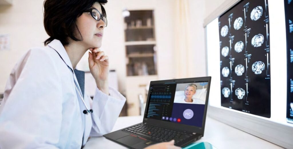 Female doctor sitting with a laptop, joining a virtual consultation and reviewing body scan images.