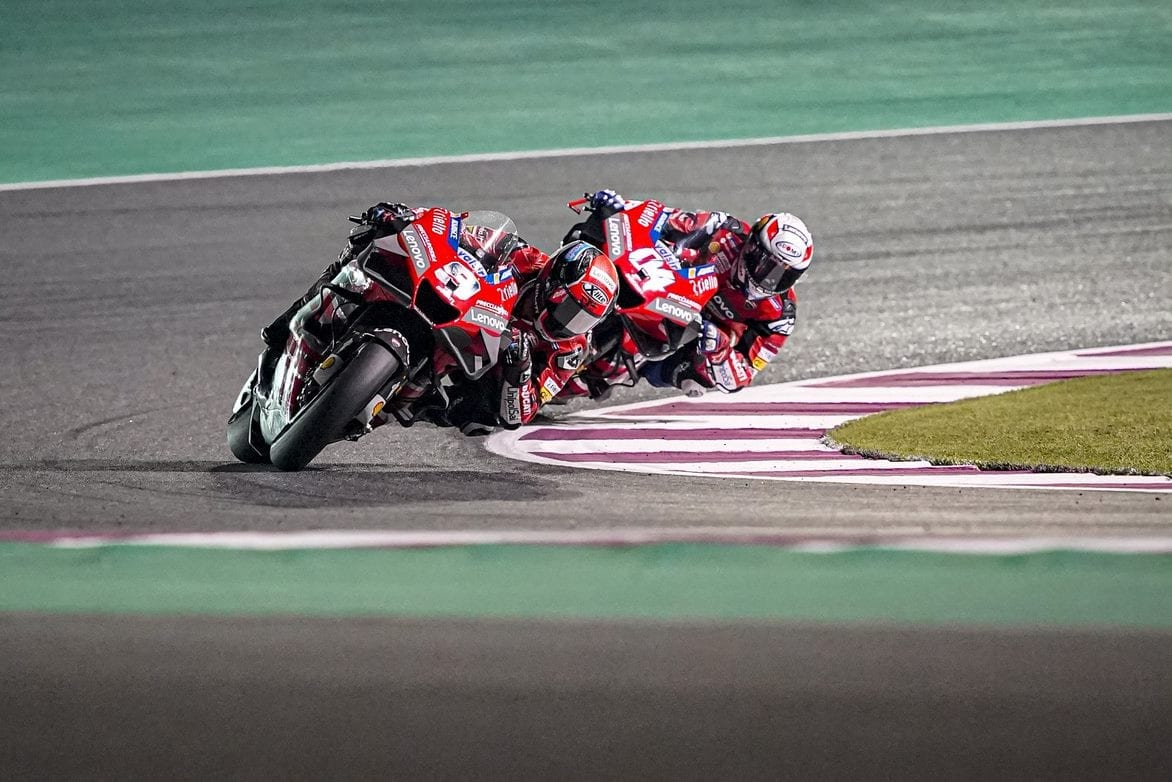 Two Ducati racers in a deep lean as they round a turn on a racetrack