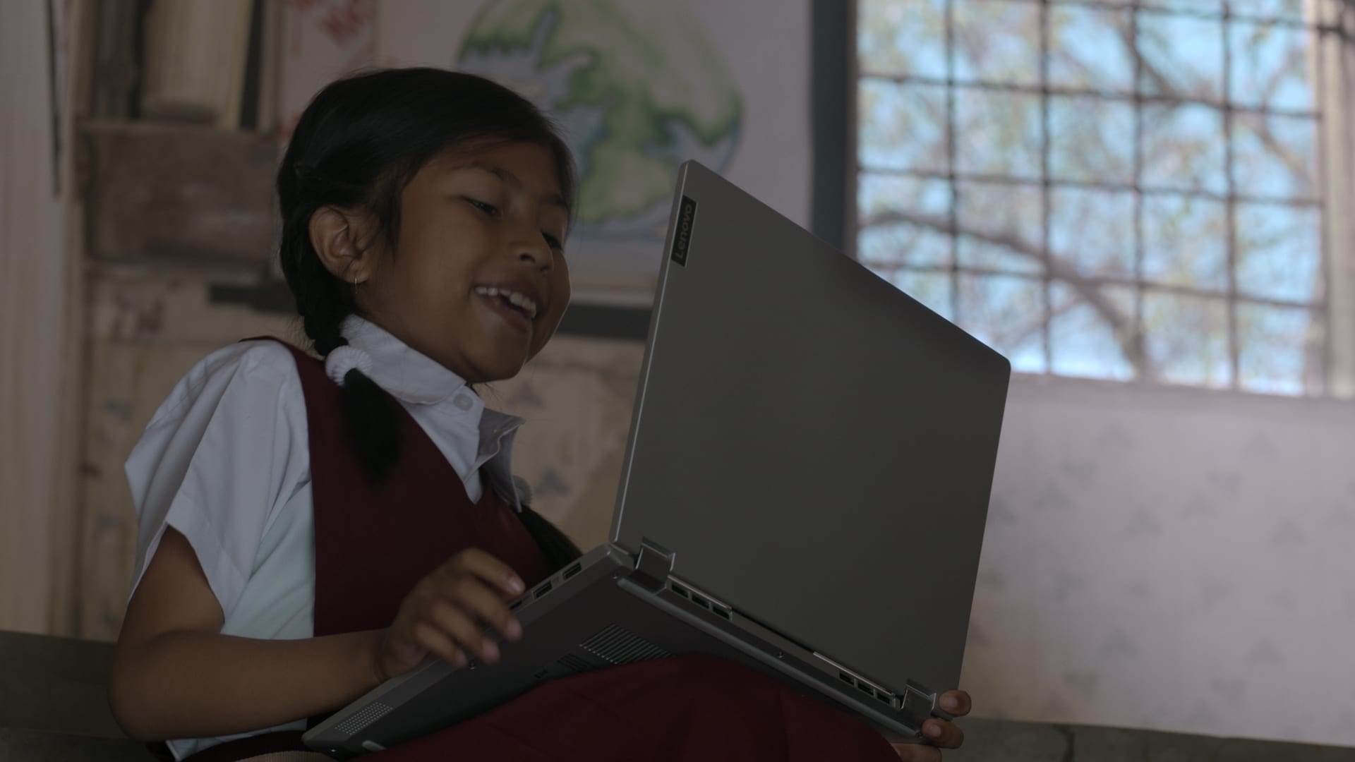 Young student with Lenovo laptop, smiling toward the screen