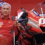Ducati Team Manager Davide Tardozzi sitting beside a MotoGP bike