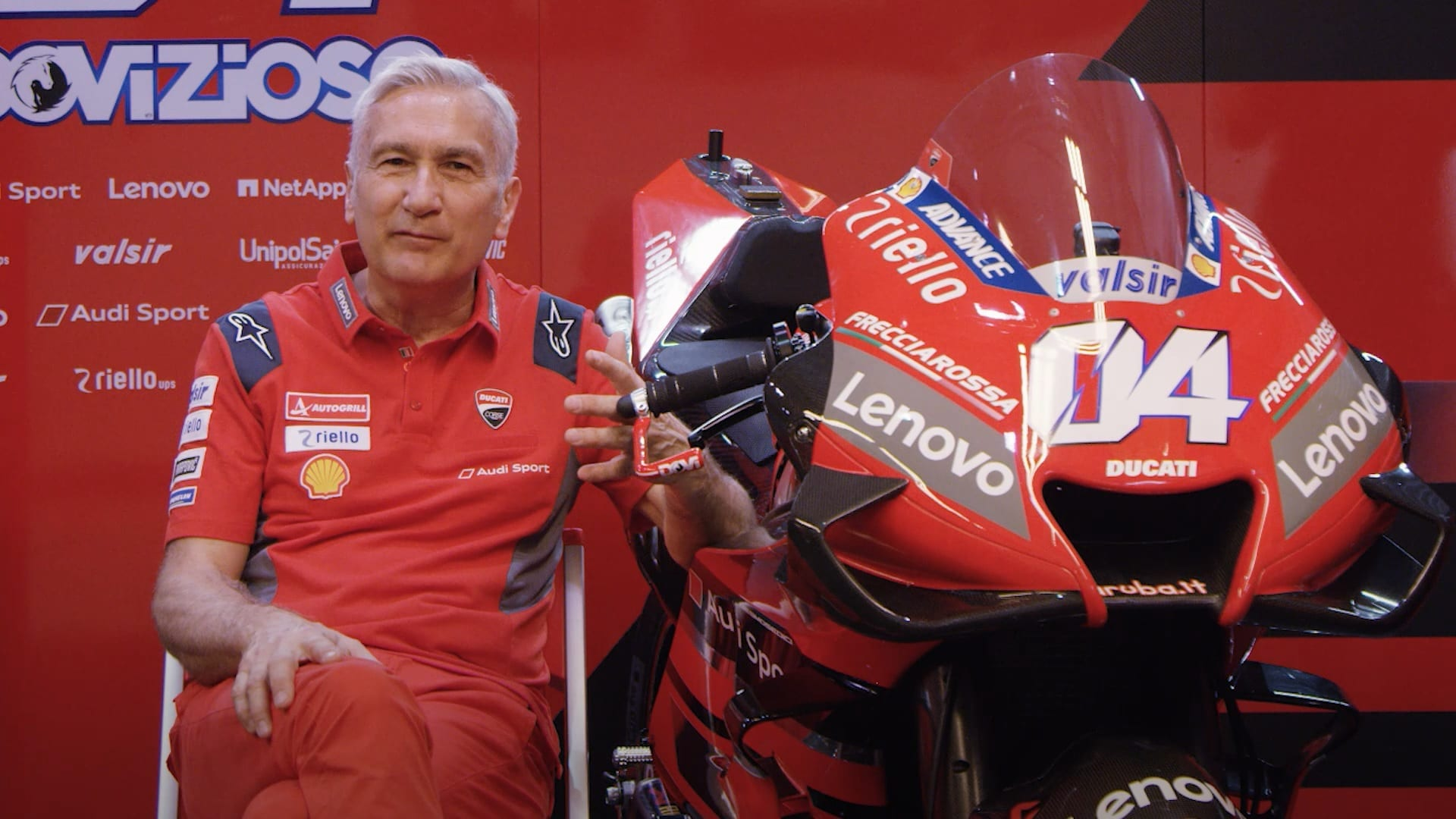 Ducati Team Manager Davide Tardozzi sitting beside a MotoGP bike