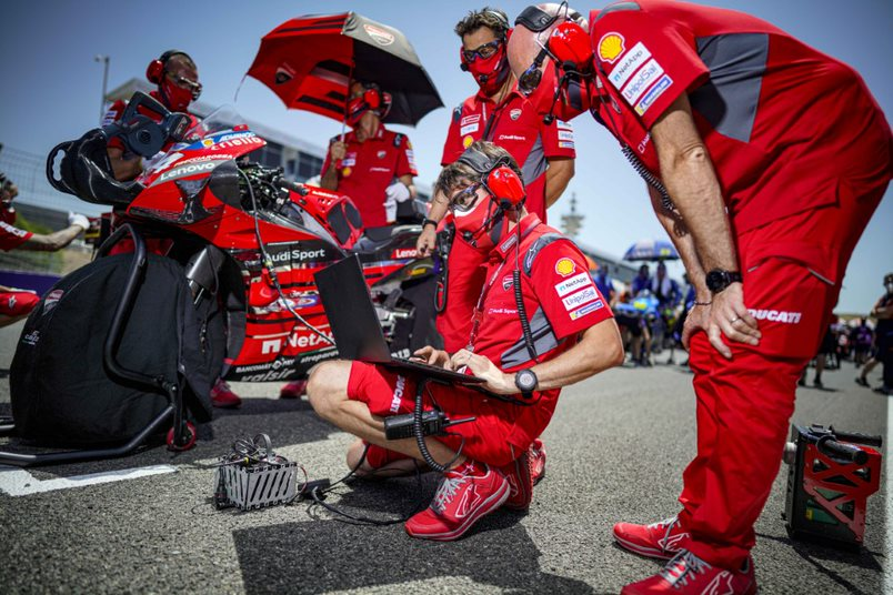 Tardozzi with a team of technicians on the MotoGP track reviewing data.
