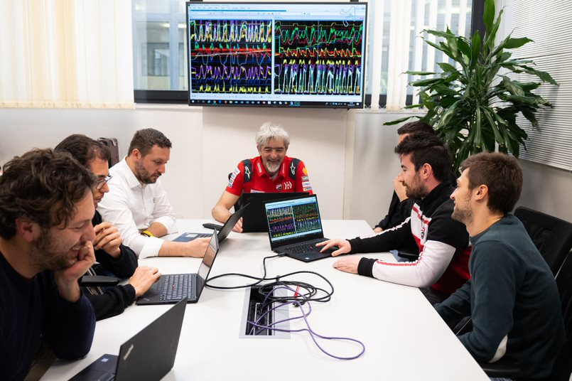 Tardozzi and team sitting around a conference room table using Lenovo devices to review data, which also streams on a monitor on the wall.