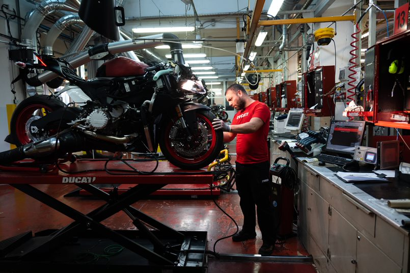 Mechanic with Ducati motorbike on elevated platform, tuning up the machine