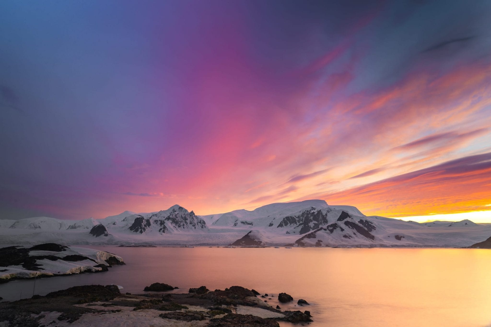 Brightly colored sunset over Antarctica's mountains.
