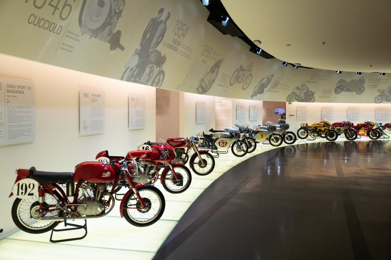 Museum display with a series of different iterations of Ducati motorbikes