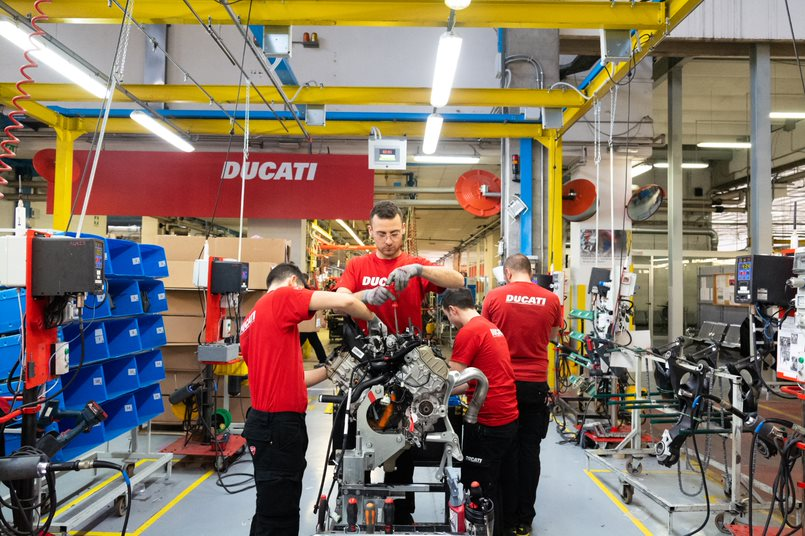 Team of Ducati mechanics and engineers working on an engine