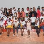 Residents of the St Monica's Child and Youth Care Centre in South Africa sitting on stage.