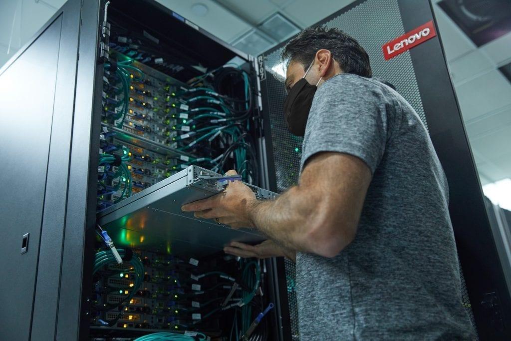Lenovo technician installing a large data center rack.