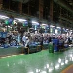 Hero MotoCorp assembly line, wide shot with multiple people working on dozens of motorcycles.