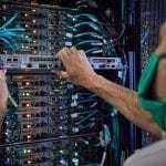 Person installing a panel in a Lenovo data center with Neptune liquid cooling technology.