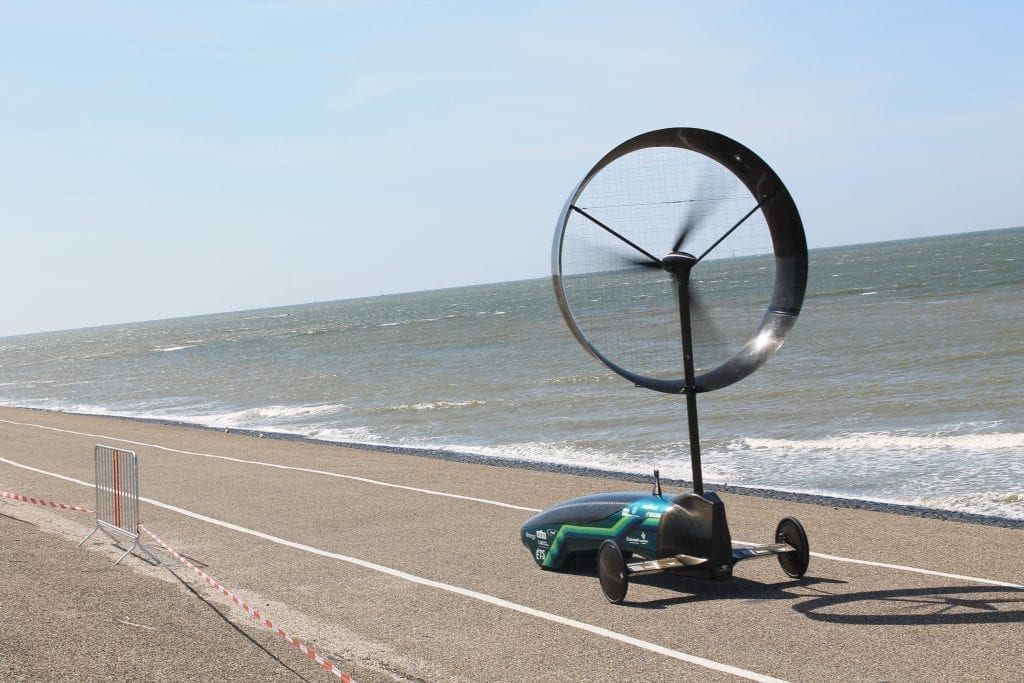 Wind-powered car by Chinook races along a coastline.