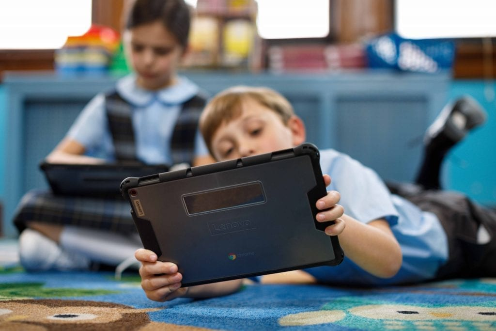 Young kid lying down and using a Lenovo tablet to learn remotely