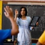 Teacher standing in front of a classroom with a Lenovo PC, calling a student who is raising his hand.