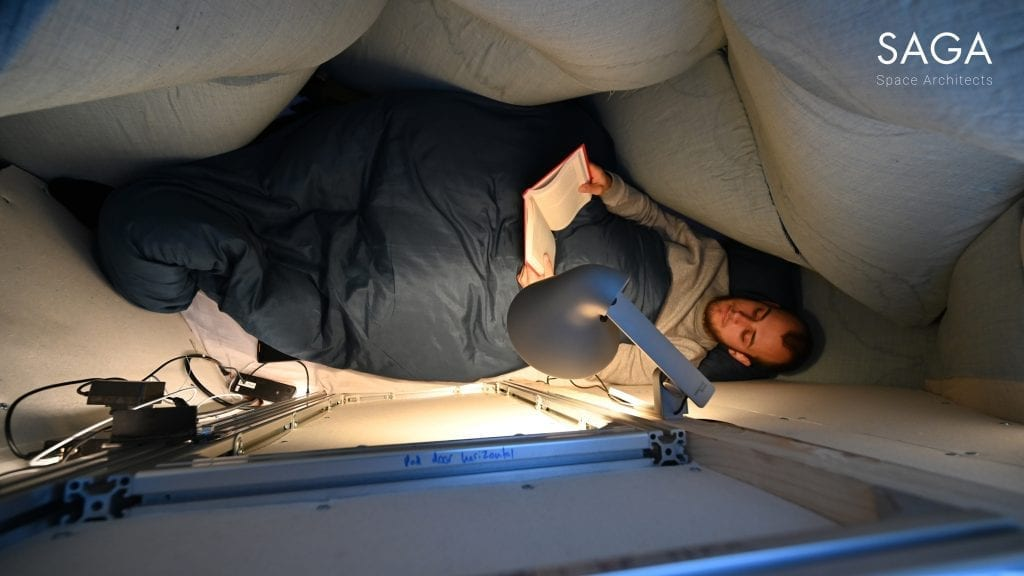 Sebastian lying down reading in the Lunark module, tucked into a sleeping bag.