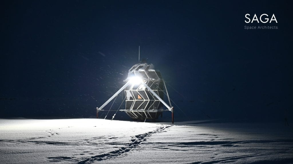 Lunark module sitting in the snow at night with bright light illuminating the surrounding snow.