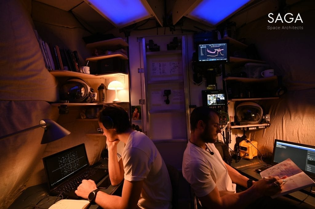 Sebastian and Karl in the module at night, sitting at different workstations with multiple monitors.
