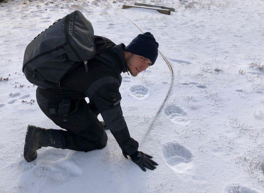 Sebastian outside in the snow examining polar bear tracks.