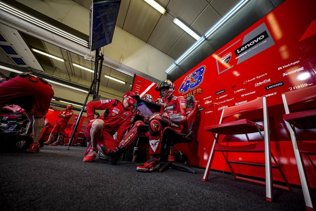 Ducati driver sitting and reviewing data on a laptop while consulting with another team member