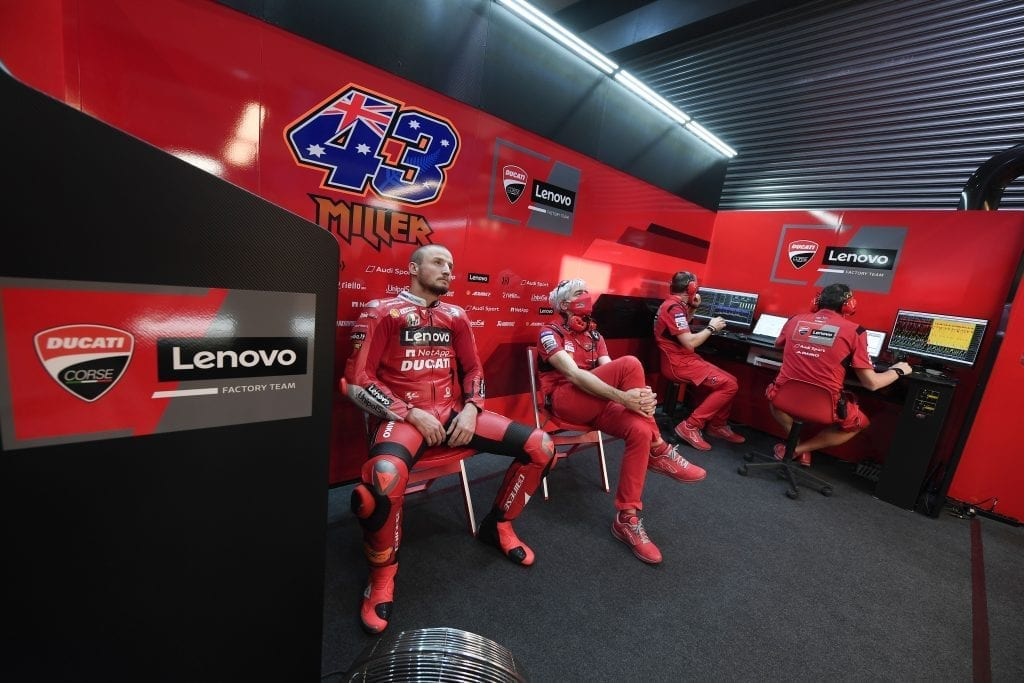 Ducati team dressed in bright red, some waiting while others review data