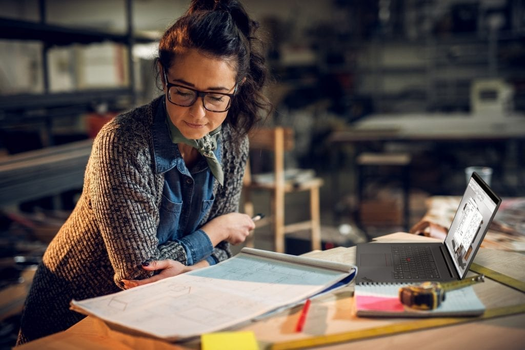 Woman with architectural drafting pads working with a Lenovo ThinkPad P1 Gen 4