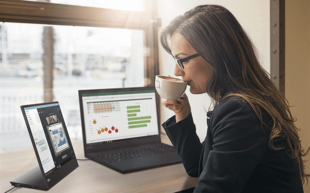 Woman reviewing content on ThinkVision M15 mobile monitor while sipping coffee