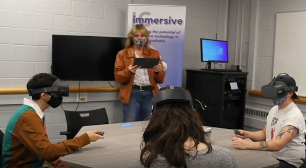 Three students at Ithaca College use Lenovo VR Classroom solutions to learn as they sit around a table wearing VR headsets.