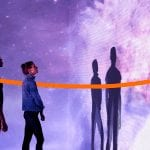 Lenovo Beyond Boundaries image - orange ribbon moving between two people looking at a wall covered in projected nebulae